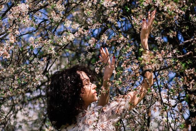 Giovane donna attraente con capelli lunghi ricci in posa nel giardino fiorito primaverile