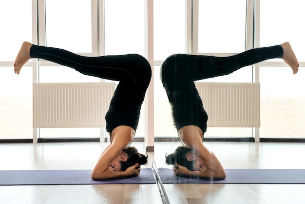 Giovane donna attraente yogi che pratica il concetto di yoga, in piedi nell'esercizio di salamba sirsasana