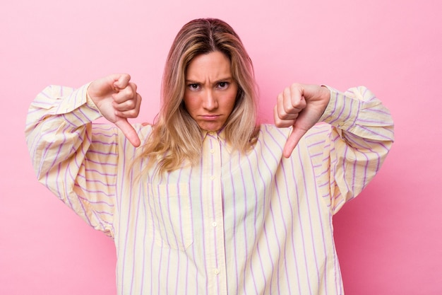 Giovane donna australiana isolata mostrando un gesto di antipatia, pollice in giù. concetto di disaccordo.