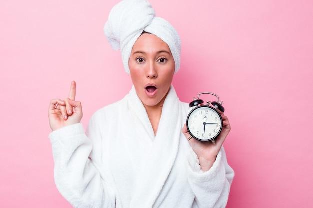 Giovane donna australiana che lascia la doccia in ritardo isolata su sfondo rosa con qualche grande idea, concetto di creatività.