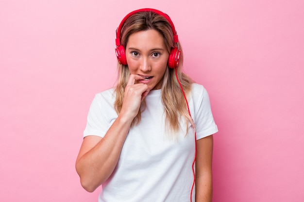 Giovane donna australiana che ascolta musica isolata su sfondo rosa che si morde le unghie, nervosa e molto ansiosa.