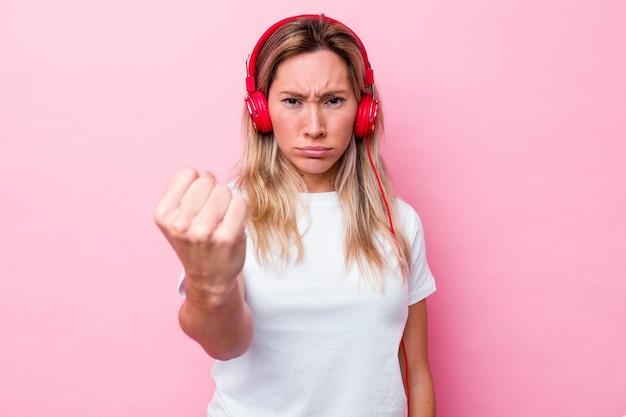 Musica d'ascolto della giovane donna australiana isolata su fondo rosa che mostra il pugno alla macchina fotografica, espressione facciale aggressiva.