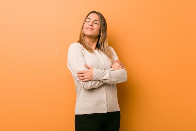 Giovane donna autentica carismatica vera gente contro un abbraccio di muro, sorridente spensierato e felice.