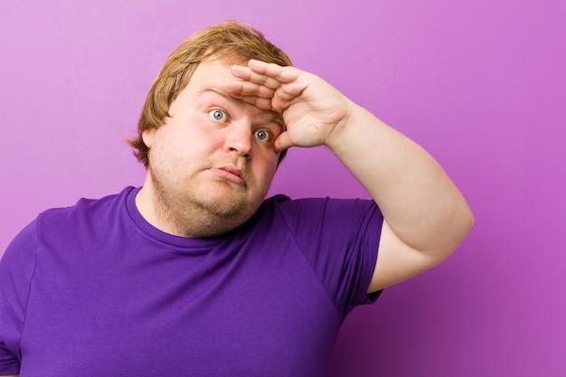 Giovane uomo grasso della testarossa autentica che guarda lontano tenendo la mano sulla fronte.