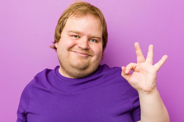 Giovane uomo autentico rossa allegro e fiducioso mostrando gesto ok
