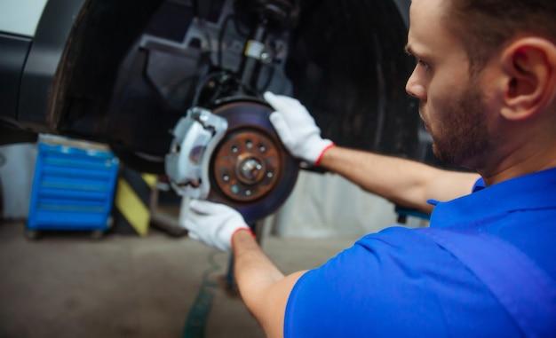 Il giovane meccanico in una tuta speciale ripara il sistema frenante di un'auto o cambia le pastiglie dei freni