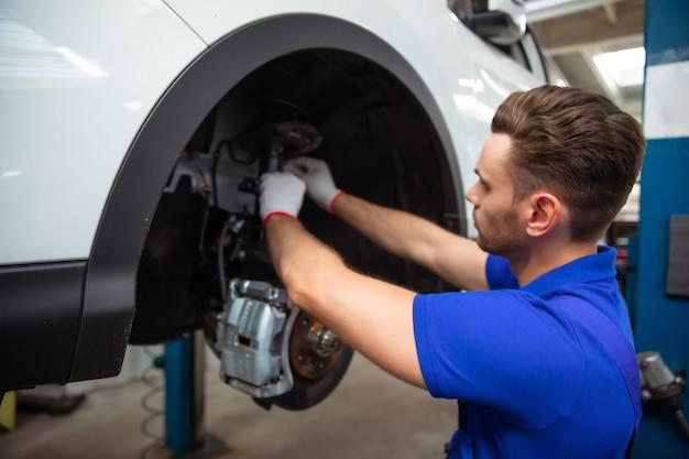 Il giovane meccanico in una tuta speciale ripara il sistema frenante di un'auto o cambia le pastiglie dei freni Foto Premium