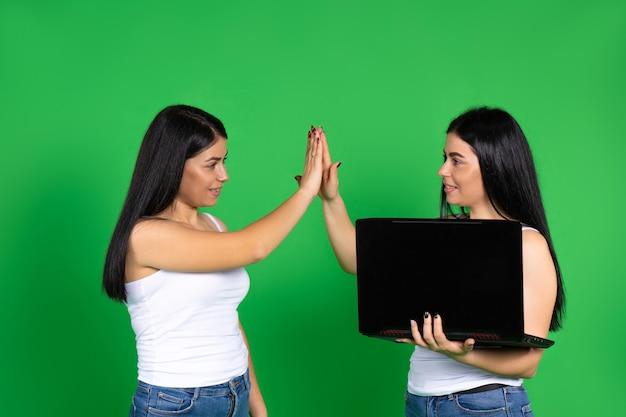Le giovani sorelle gemelle fantastiche con il laptop si rallegrano del loro successo