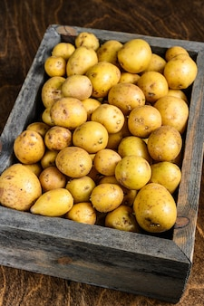 Young baby patate in una scatola di legno