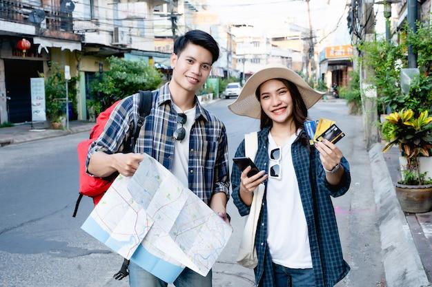 Giovane zaino in spalla che tiene una mappa cartacea e una bella donna indossa un sombrero che tiene lo smartphone e mostra la carta di credito in mano, li usano per il pagamento per il viaggio con felicità in vacanza