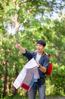Giovane viaggiatore con lo zaino in spalla che tiene in mano una mappa cartacea, porta un grande zaino durante il relax all'aperto durante le vacanze estive in prova nella foresta, copia spazio