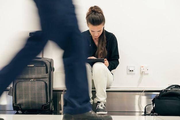 Giovane donna zaino in spalla che aspetta il suo volo all'aeroporto