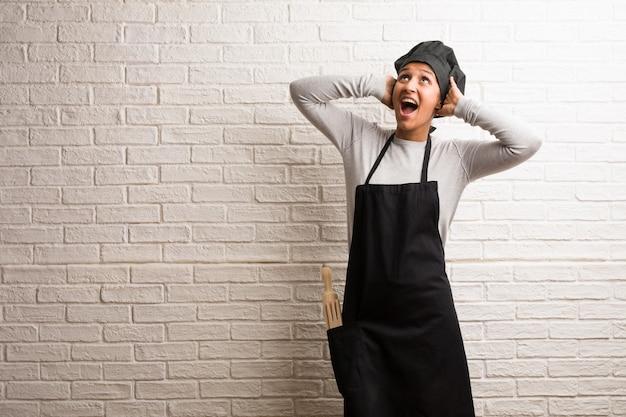 Donna indiana giovane panettiere contro un muro di mattoni sorpreso e scioccato, guardando con gli occhi spalancati