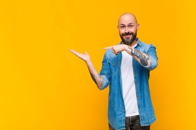 Giovane uomo calvo e barbuto che sorride allegramente e punta a copiare lo spazio sul palmo sul lato, mostrando o pubblicizzando un oggetto