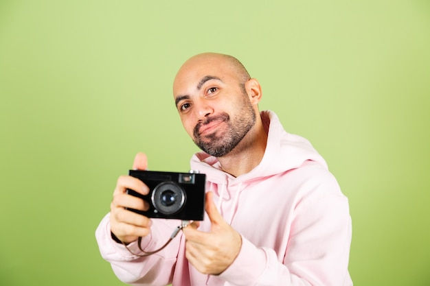 Giovane uomo caucasico calvo in felpa con cappuccio rosa isolato, pantaloni a vita bassa positiva tenere la fotocamera