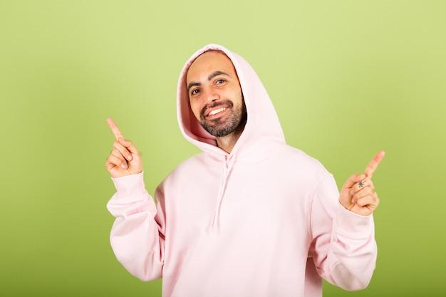 Il giovane uomo caucasico calvo in felpa con cappuccio rosa punta il dito verso l'alto