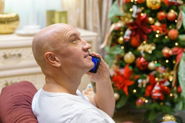 Il giovane uomo calvo e felice si siede davanti all'albero di natale decorato nel suo appartamento e parla al telefono c...