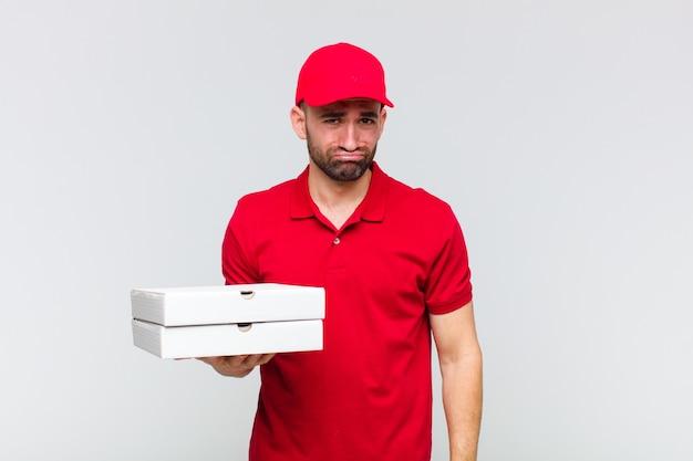 Giovane uomo calvo che si sente triste e piagnucoloso con uno sguardo infelice, piange con un atteggiamento negativo e frustrato Foto Premium