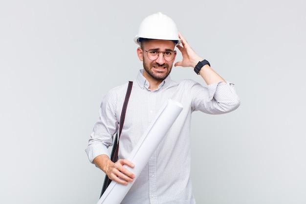 Giovane uomo calvo che si sente stressato, preoccupato, ansioso o spaventato, con le mani sulla testa, in preda al panico per errore