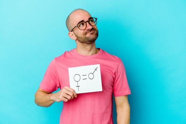 Giovane uomo calvo che tiene un cartello di uguaglianza di genere isolato sulla parete gialla che sogna di raggiungere obiettivi e scopi