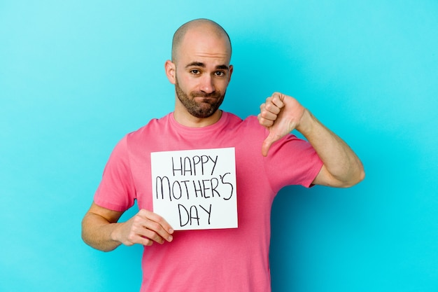 Giovane uomo calvo che tiene un cartello di giorno di madri felice isolato sulla parete blu che mostra un gesto di avversione, pollice in giù. concetto di disaccordo