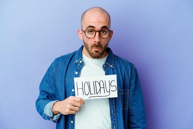 Giovane uomo calvo che tiene un cartello di vacanze isolato sulla parete blu alza le spalle e gli occhi aperti confusi
