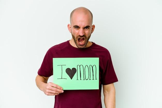 Giovane uomo calvo che tiene un cartello di i love mom isolato sulla parete gialla che grida molto arrabbiato e aggressivo