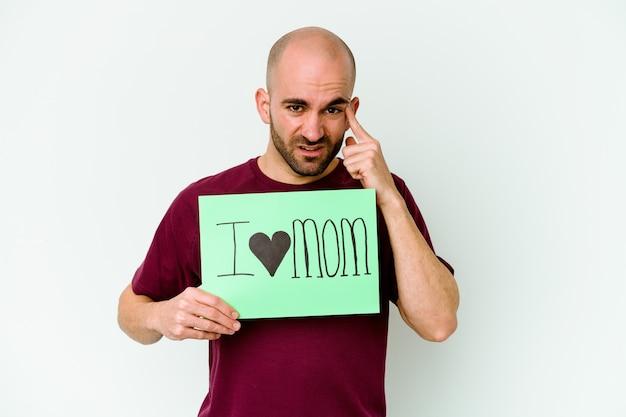 Giovane uomo calvo che tiene un cartello di i love mom isolato sulla parete gialla che mostra un gesto di delusione con l'indice