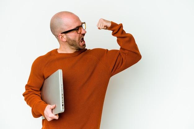 Giovane uomo calvo che tiene un computer portatile isolato su fondo bianco che alza il pugno dopo una vittoria, concetto del vincitore.