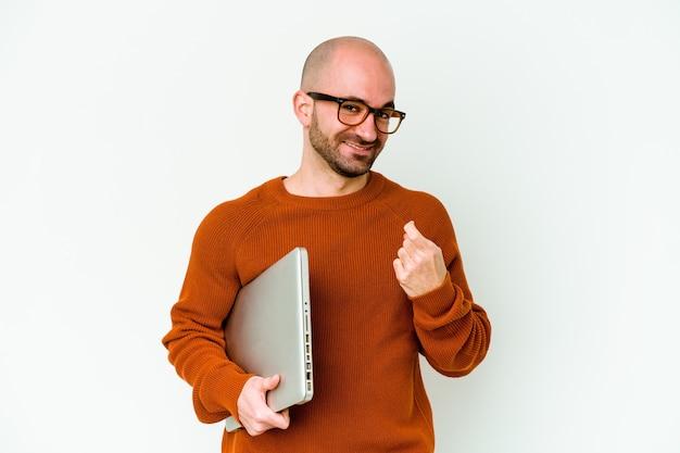 Giovane uomo calvo che tiene un computer portatile isolato sul muro bianco che punta il dito contro di te come se invitando ad avvicinarsi