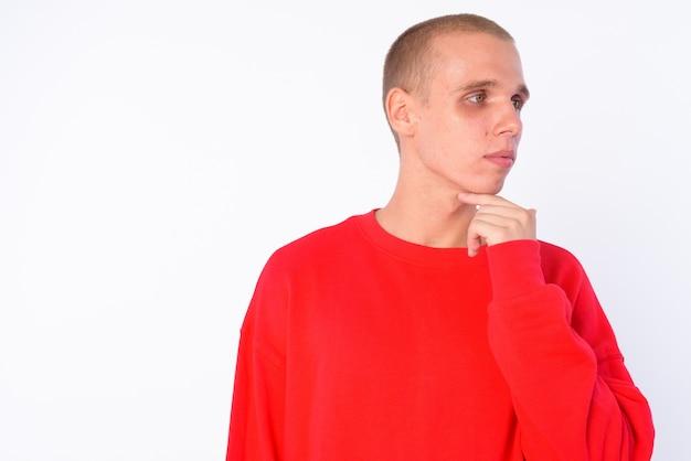 Giovane uomo calvo isolato contro il muro bianco