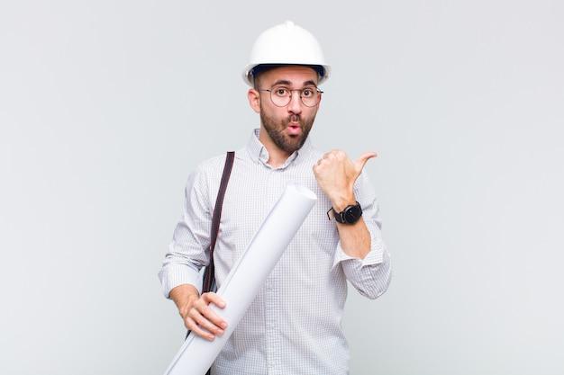 Giovane uomo calvo che guarda stupito incredulo, indicando un oggetto sul lato e dicendo wow, incredibile