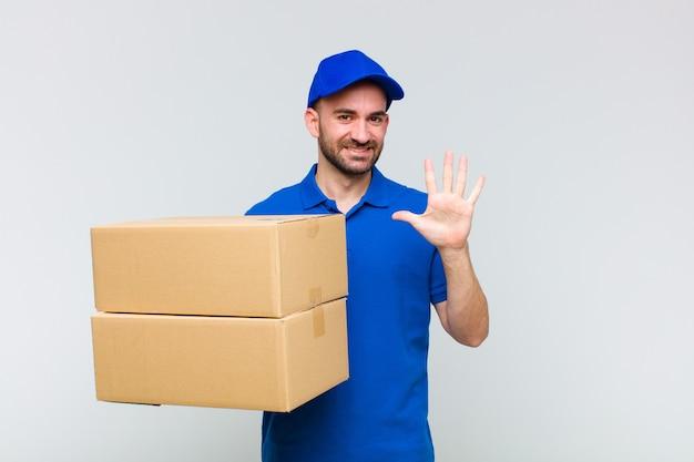 Giovane uomo calvo sorridente e guardando amichevole, mostrando il numero cinque o quinto con la mano in avanti, il conto alla rovescia