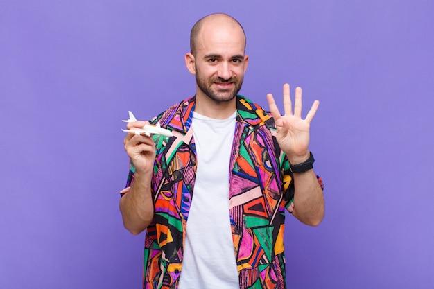 Giovane uomo calvo sorridente e guardando amichevole, mostrando il numero quattro o quarto con la mano in avanti, il conto alla rovescia