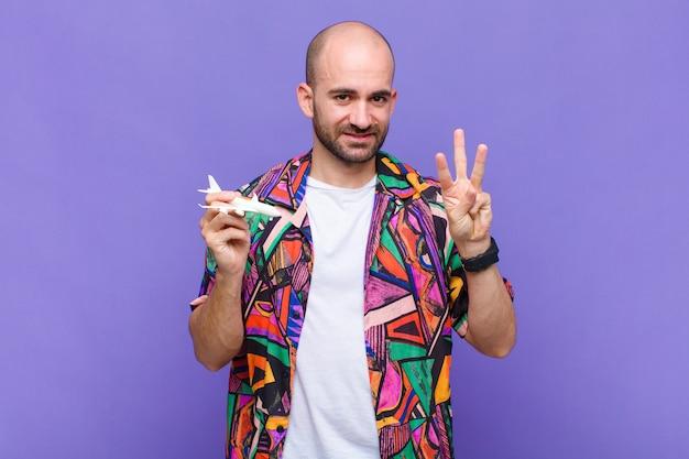 Giovane uomo calvo sorridente e guardando amichevole, mostrando il numero tre o terzo con la mano in avanti, il conto alla rovescia