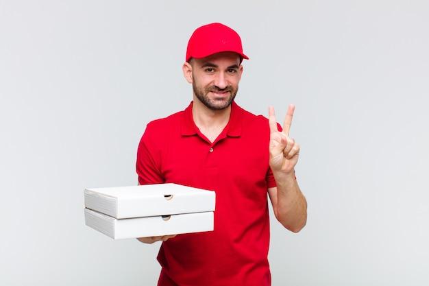 Giovane uomo calvo sorridente e guardando amichevole, mostrando il numero due o secondi con la mano in avanti, conto alla rovescia