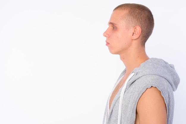 Giovane uomo ribelle calvo che indossa camicia con cappuccio isolata contro il muro bianco