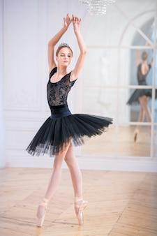 Giovane ballerina in tutù nero balla sulle punte in un ampio salone luminoso davanti a uno specchio.