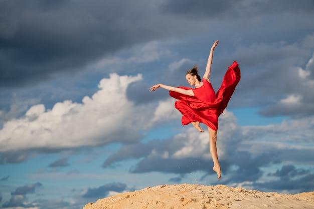 Giovane ballerina in un vestito rosso si bloccò in un salto contro un cielo blu