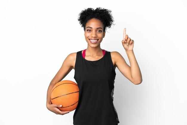 Giovane giocatore di basket donna latina isolata su sfondo bianco che punta verso l'alto una grande idea