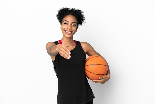 Giovane giocatore di basket donna latina isolata su sfondo bianco che stringe la mano per chiudere un buon affare