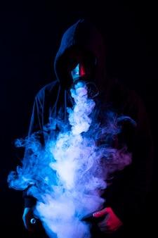 Giovane barbuto uomo arabo che fuma vape e fa trucchi con luci colorate. verticale