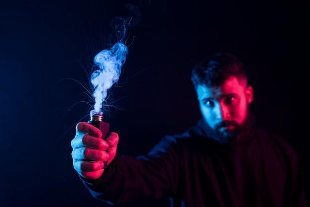Giovane barbuto uomo arabo che fuma vape e fa trucchi con luci colorate.