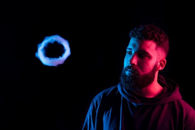 Giovane barbuto uomo arabo che fuma vape e fa anelli di fumo con luci colorate. copia spazio.