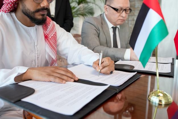 Giovane uomo d'affari arabo barbuto o delegato in abiti nazionali che firma un contratto di partnership commerciale tra il suo paese e la russia