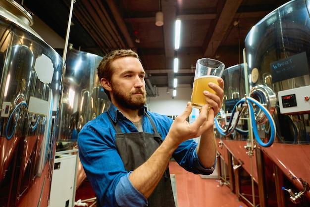 Giovane birraio barbuto con un bicchiere di birra che valuta le sue caratteristiche visive dopo la preparazione mentre si trova davanti alla telecamera