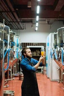 Giovane birraio barbuto in abiti da lavoro guardando un bicchiere di birra in mano dopo la preparazione mentre si trova nel corridoio tra enormi serbatoi di acciaio