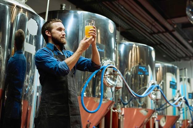 Giovane mastro birraio barbuto con un bicchiere di birra in mano che ne valuta le caratteristiche visive dopo la preparazione durante il lavoro nell'impianto di lavorazione