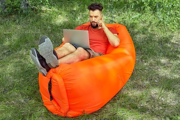 Giovane uomo d'affari barbuto è sdraiato sul divano ad aria sull'erba e lavora usando il suo laptop e parla al telefono durante l'ecoturismo.