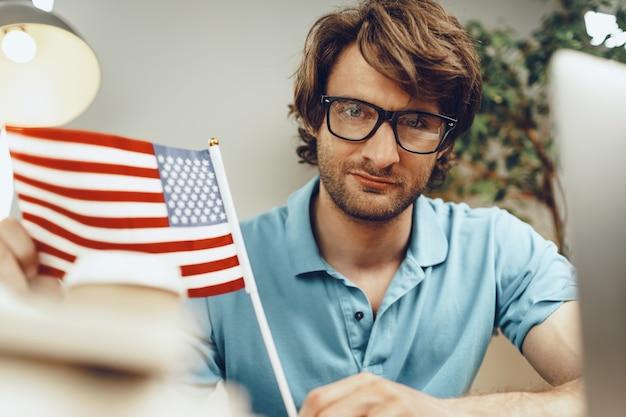 Giovane imprenditore barbuto seduto a tavola con laptop e bandiera americana
